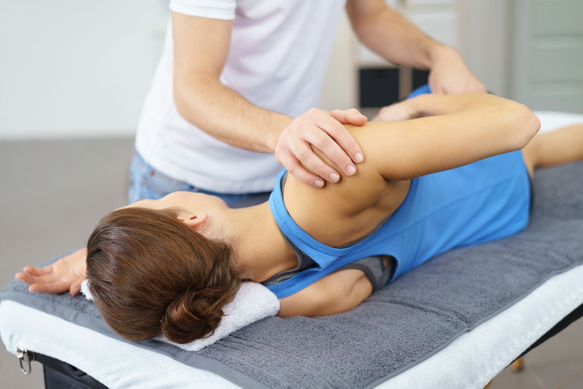 49086034 - male osteopath stretching the injured body of his female patient lying on a therapy bed.